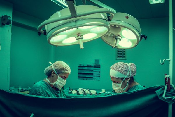 two person doing surgery inside room